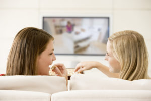 two female friends watching television